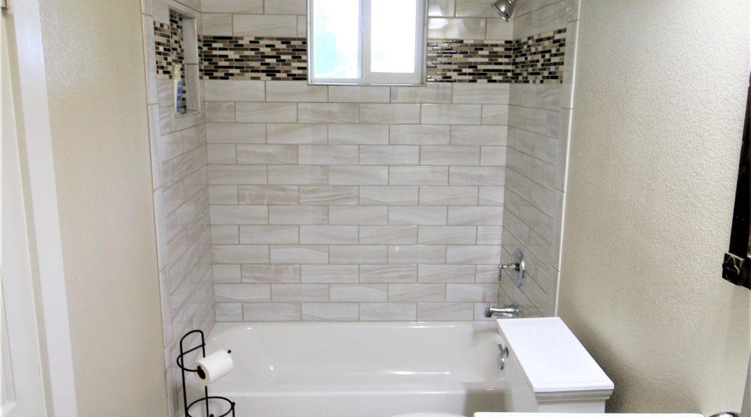 remodeled bathroom with shower backsplash and glass door